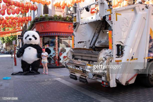 Rubbish truck passes some people trying to earn some money from tourists dressed up as a Giant Panda on the corner of Gerrard Street in Chinatown...