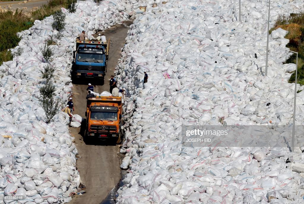 Rubbish trucks drive between a built up pile of waste on a street in Beirut's northern suburb of Jdeideh on February 25, 2016. Lebanon canceled a plan to export its waste to Russia, sending Beirut's six-month garbage crisis back to square one as mountains of trash choke the city's air and streets. / AFP / JOSEPH EID