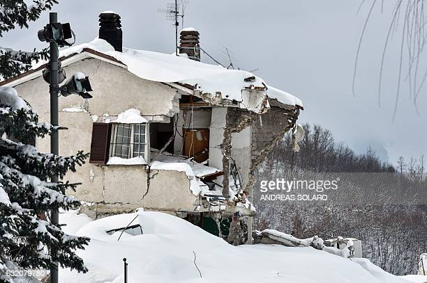 TOPSHOT Rubble and debris of a building destroyed in an August 2016 quake are covered with snow in the damaged central Italian village of Amatrice...