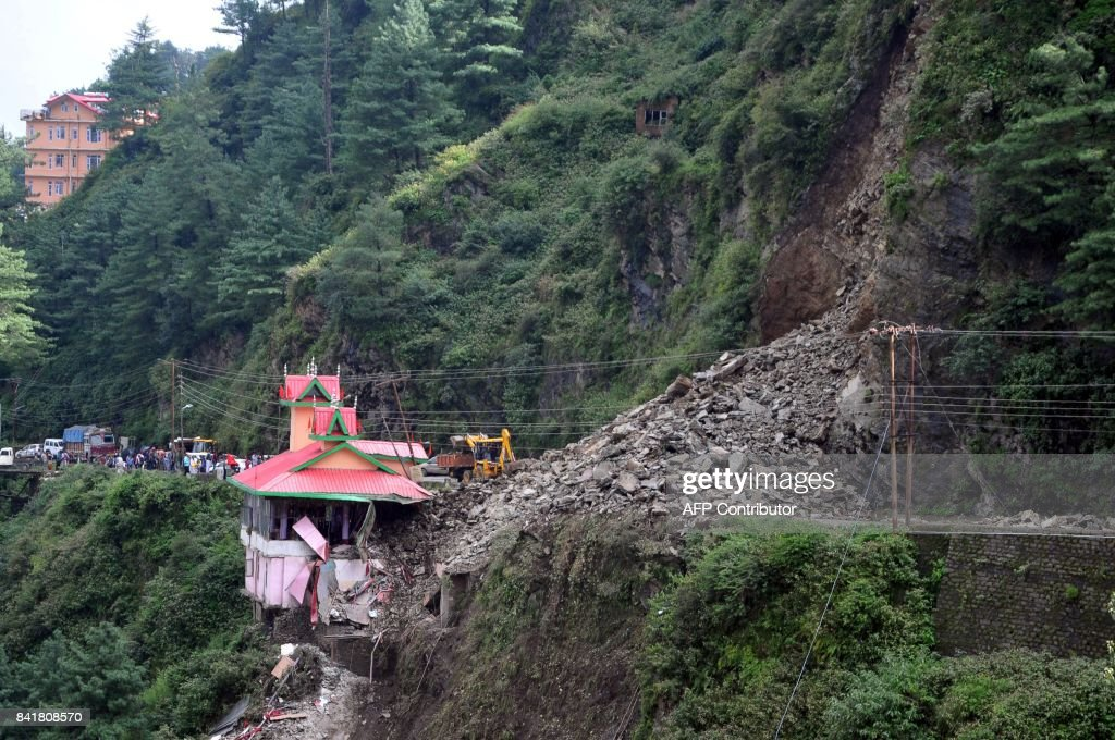 Rubble blocks the ChandigarhShimla national highway after a landslide buried at least six vehicles next to a temple in Bhattakufer in the Indian...