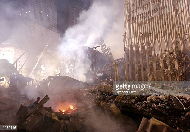 Rubble burns at the remains of the destroyed World Trade Center towers September 12 2001 in New York City
