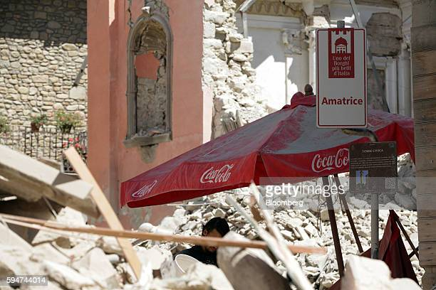 Rubble covers the street as a CocaCola Co branded parasol stands following an earthquake in Amatrice Italy on Wednesday Aug 24 2016 A powerful...