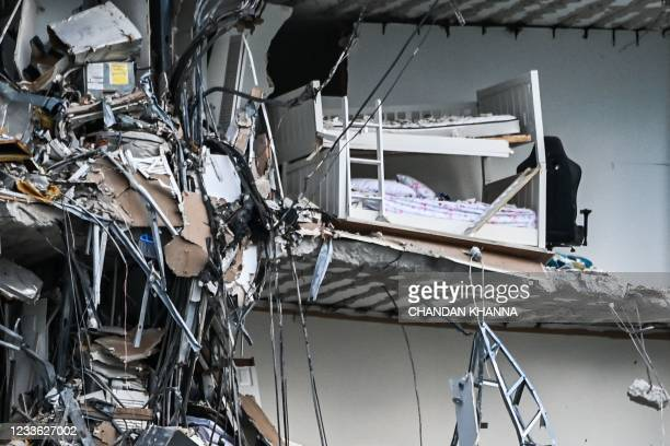 Rubble hangs from a partially collapsed building in Surfside north of Miami Beach, on June 24, 2021. - The multi-story apartment block in Florida...