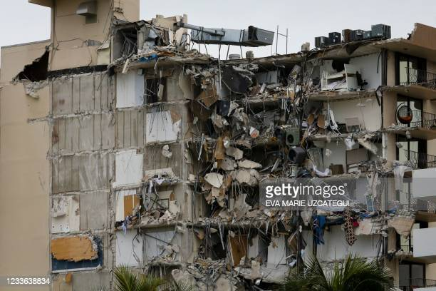 Rubble hangs from a partially collapsed building in Surfside north of Miami Beach, on June 24, 2021. - A high-rise oceanfront apartment block near...