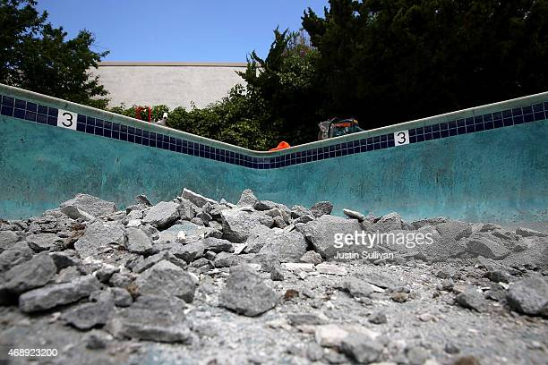 Rubble sits on the bottom of a swimming pool as work crews begin demolition of the pool at an apartment complex on April 8 2015 in Hayward California...
