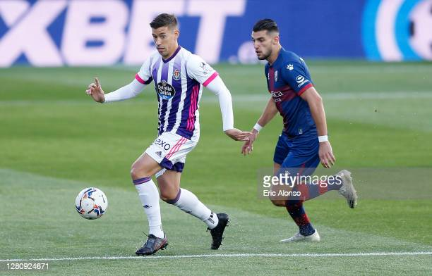 Ruben Alcaraz of Real Valladolid is challenged by Rafa Mir of SD Huesca during the La Liga Santander match between SD Huesca and Real Valladolid CF...