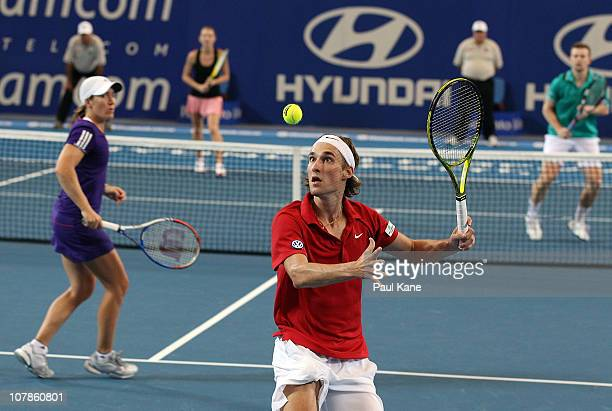 Ruben Bemelmans of Belgium plays a return shot during his mixed doubles match partnered with Justine Henin against Andrey Golubev and Sesil...