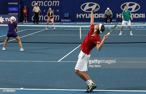 Ruben Bemelmans of Belgium serves during his mixed doubles match partnered with Justine Henin against Andrey Golubev and Sesil Karatantcheva of...