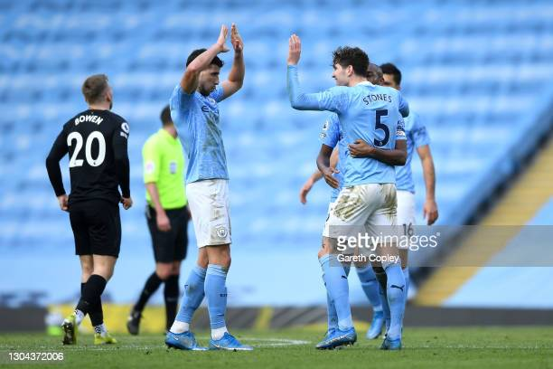 Ruben Dias and John Stones of Manchester City celebrate following their team's victory in the Premier League match between Manchester City and West...