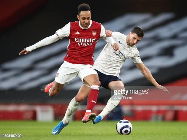 Ruben Dias of Manchester City battles for possession with Pierre Emerick Aubameyang of Arsenal during the Premier League match between Arsenal and...