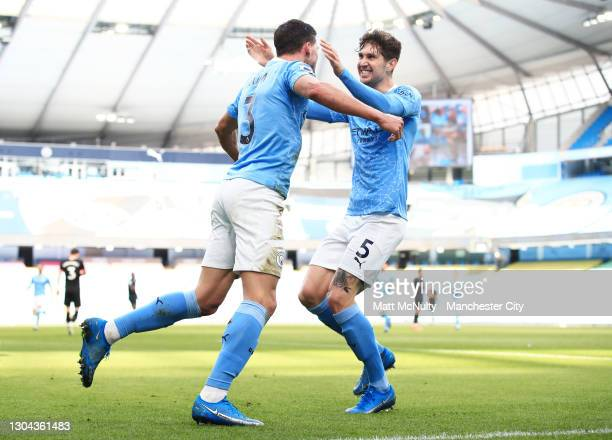 Ruben Dias of Manchester City celebrates with teammate John Stones after scoring his team's first goal during the Premier League match between...
