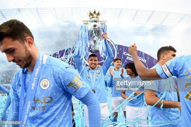 Ruben Dias of Manchester City celebrates with the Premier League Trophy as Manchester City are presented with the Trophy as they win the league...