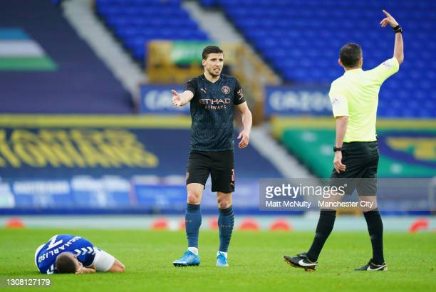Ruben Dias of Manchester City gestures as Richarlison of Everton lies injured during The Emirates FA Cup Quarter Final match between Everton v...