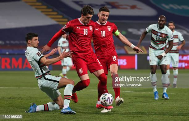Ruben Dias of Portugal and Dušan Vlahovic and Dusan Tadic of Serbia battle for the ball during the FIFA World Cup 2022 Qatar qualifying match between...