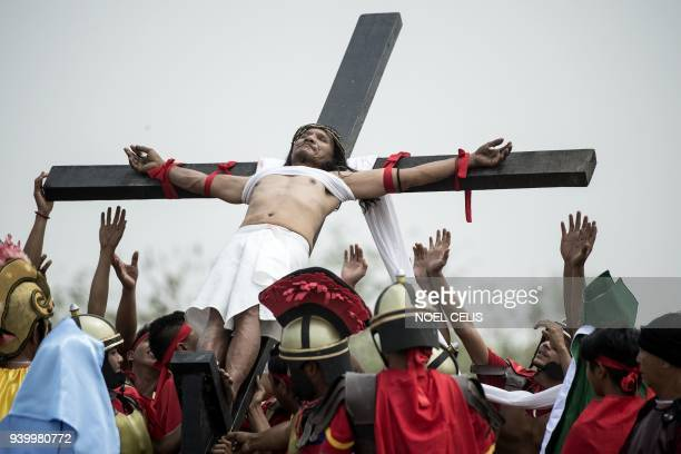 Ruben Enaje a Christian devotee reacts as he is nailed to a cross during a reenactment of the crucifixion of Jesus Christ during Good Friday...