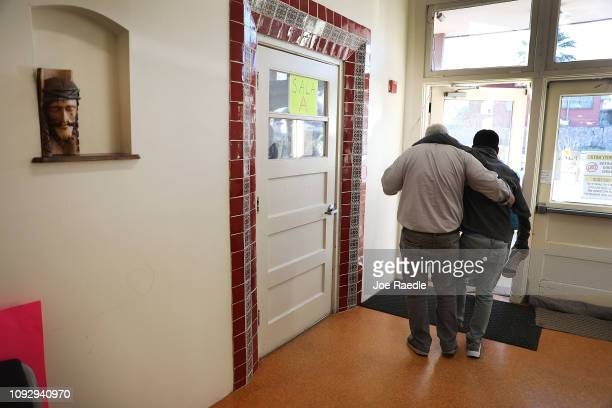 Ruben Garcia director of the Annunciation House helps a young injured immigrant to his vehicle January 11 2019 in El Paso Texas The immigrant hurt...
