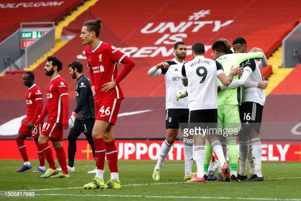Ruben Loftus-Cheek of Fulham celebrates victory with team mates as Rhys Williams of Liverpool looks dejected following the Premier League match...
