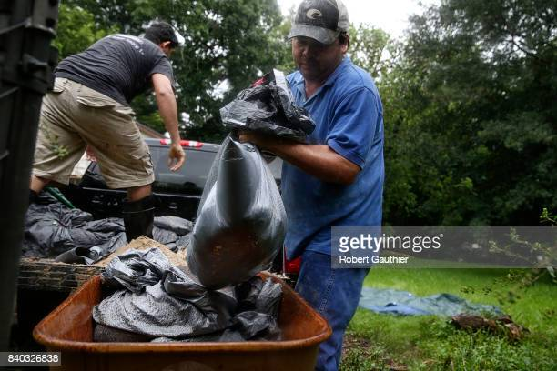 Ruben Lozano and Javier Escamilla create makeshift sandbags in an effort to ward off the surging Brazos River from their home in Reyes Trailer Park