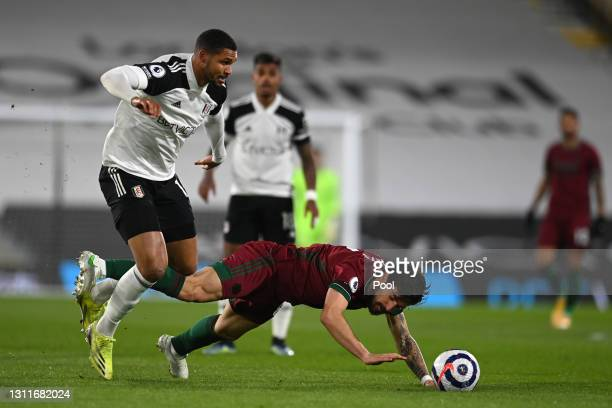 Ruben Neves of Wolverhampton Wanderers is brought down by Ruben Loftus-Cheek of Fulham during the Premier League match between Fulham and...