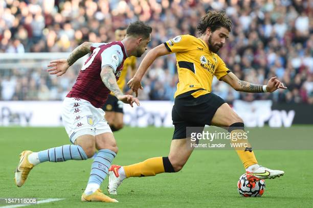 Ruben Neves of Wolverhampton Wanderers is challenged by Danny Ings of Aston Villa during the Premier League match between Aston Villa and...