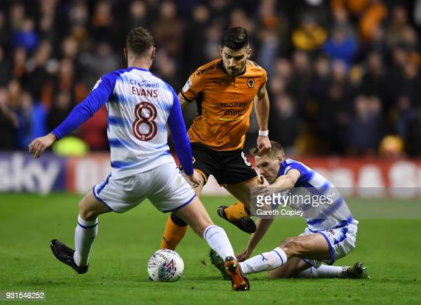 Ruben Neves of Wolverhampton Wanders gets to the ball ahead of George Evans and Dave Edwards of Reading during the Sky Bet Championship match between...