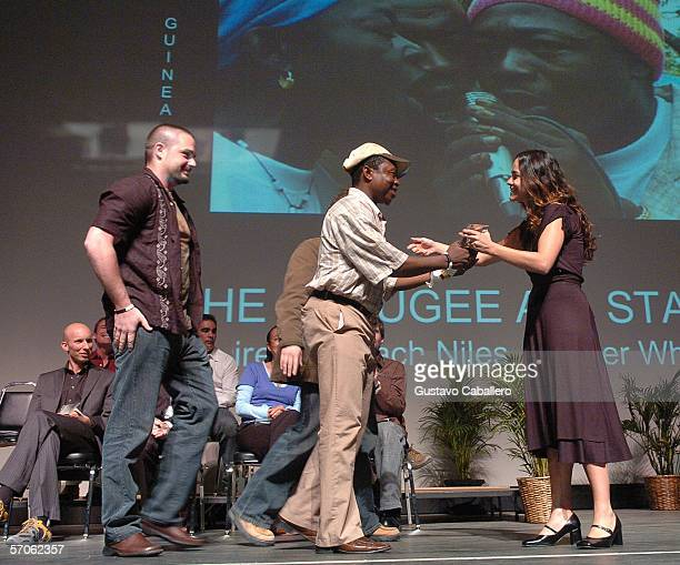 Ruben of The Refugee All Stars accepts his award from emcee Alicia Braga at the Miami International Film Festival awards ceremony at the...