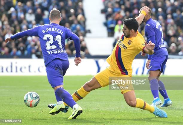 Ruben Perez of Leganes is challenged by Luis Suarez of FC Barcelona during the La Liga match between CD Leganes and FC Barcelona at Estadio Municipal...