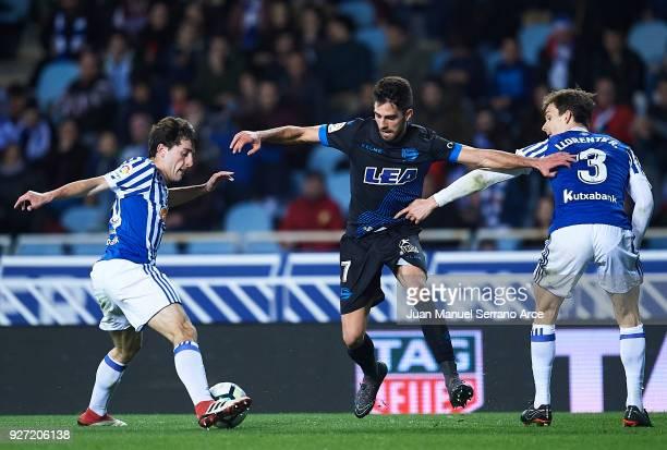 Ruben Sobrino of Deportivo Alaves being followed by Alvaro Odriozola and Diego Llorente of Real Sociedad during the La Liga match between Real...