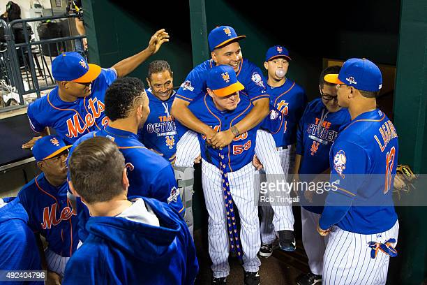 Ruben Tejada of the New York Mets receives a piggy back ride from teammate Kelly Johnson before Game 3 of the NLDS against the Los Angeles Dodgers at...