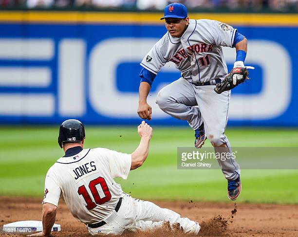 Ruben Tejada of the New York Mets turns a double play over Chipper Jones of the Atlanta Braves in the seventh inning at Turner Field on September 30...