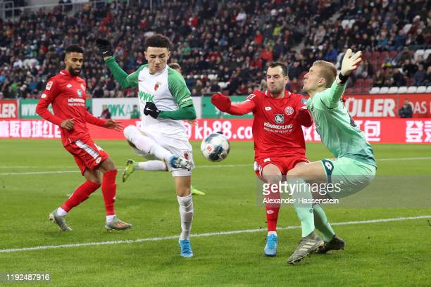 Ruben Vargas of FC Augsburg shoots as he is put under pressure by Levin Oztunali and Robin Zentner of 1. FSV Mainz 05 during the Bundesliga match...