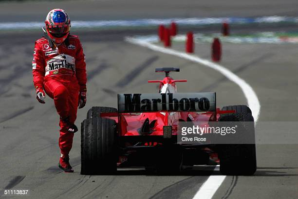Rubens Barrichello of Brazil and Ferrari looks at his flat tyre after crossing the line during the German F1 Grand Prix at the Hockenheim Circuit on...