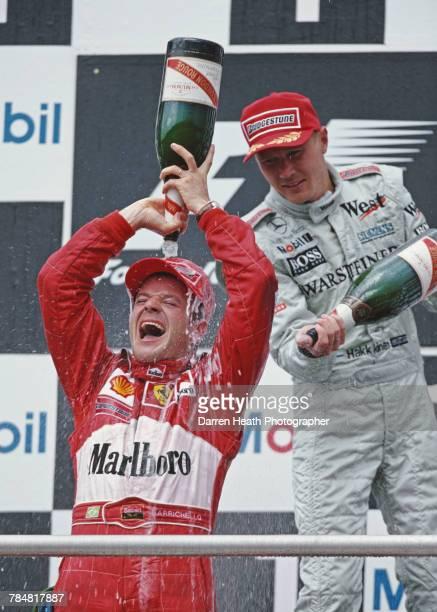 Rubens Barrichello of Brazil, driver of the Scuderia Ferrari Marlboro Ferrari F1-F2000 Ferrari V10 pours Mumm Cordon Rouge Champagne over himself as...