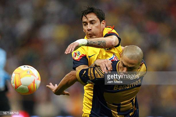 Rubens Sambueza of America struggles for the ball with Dario Veron of Pumas during a match between America and Pumas as part of the Clausura 2013...