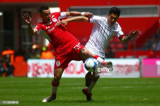 Rubens Sambueza of Toluca and Oswaldo Alanis of Chivas fight for the ball during the third round match between Toluca and Chivas as part of the...