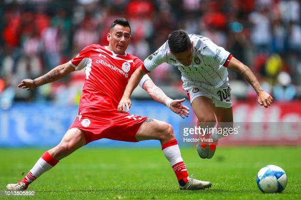 Rubens Sambueza of Toluca struggles for the ball with Edson Torres of Chivas during the third round match between Toluca and Chivas as part of the...