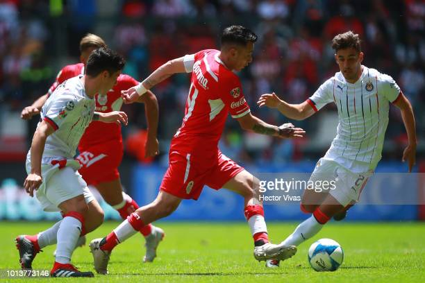 Rubens Sambueza of Toluca struggles for the ball with Josecarlos Van Rankin and Michael Perez of Chivas during the third round match between Toluca...