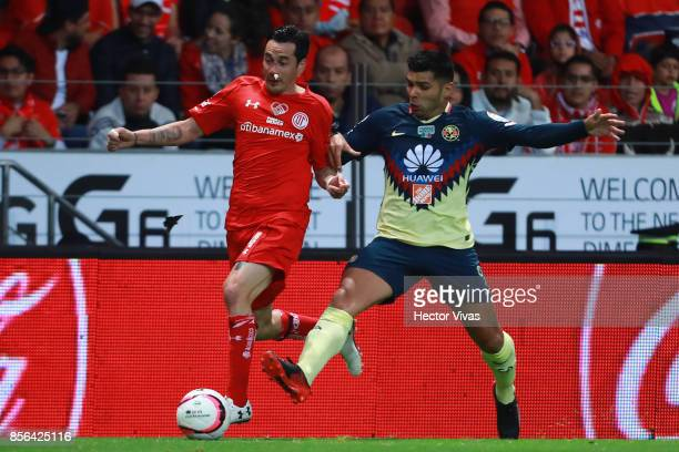 Rubens Sambueza of Toluca struggles for the ball with Silvio Romero of America during the 12th round match between Toluca and America as part of the...