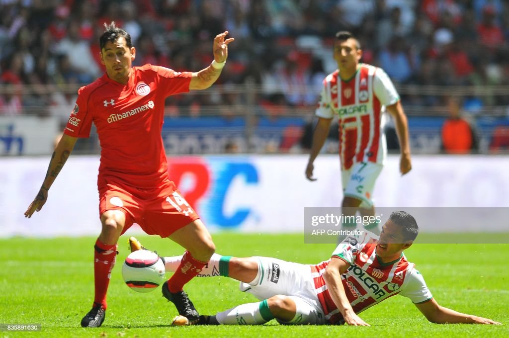 Rubens Sambueza (L) of Toluca vies for the ball with Xavier Baez of Necaxa during their Mexican Apertura football tournament match at the Nemesio Diez stadium in Toluca, Mexico, on August 20, 2017. /