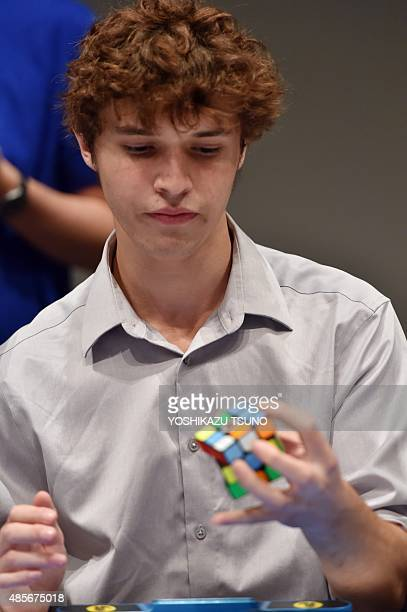 Rubic's cube contest world record holder Collin Burns from the US demonstrates his skills with one hand at a fan event of the puzzle in Tokyo on...