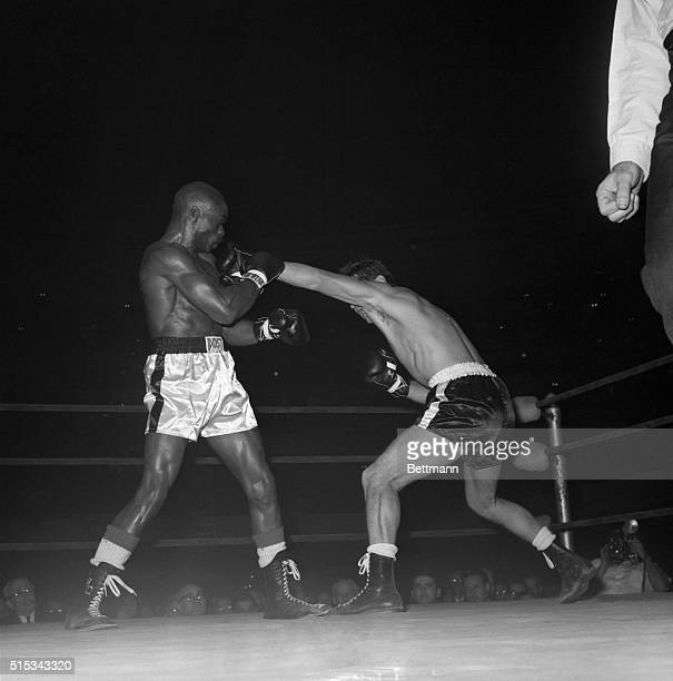 Rubin Carter is boring in but champion Joey Giardello counters deftly with a left during their middleweight title bout at Convention Hall Waging a...