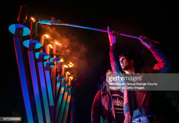 Rubin Miles right lights the last candle of the menorah during a preHanukkah celebration in Seal Beach on Sunday November 25 2018