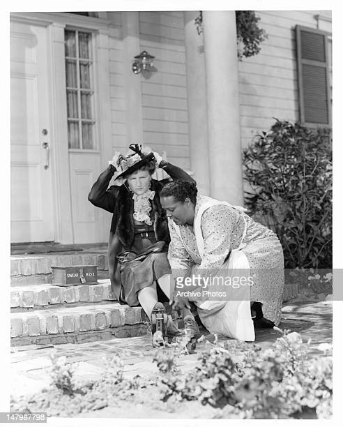 Ruby Dandridge helps Marjorie Main with her roller skates in a scene from the film 'Tish' 1942