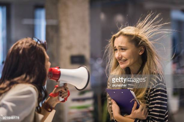 Rude female leader yelling at her coworker through megaphone.