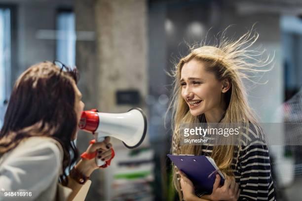 失礼な女性リーダーの彼女の同僚にメガホンで叫んで。