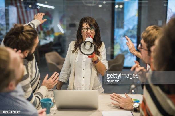 rude female leader yelling at her coworkers through megaphone in the office. - bossy stock pictures, royalty-free photos & images