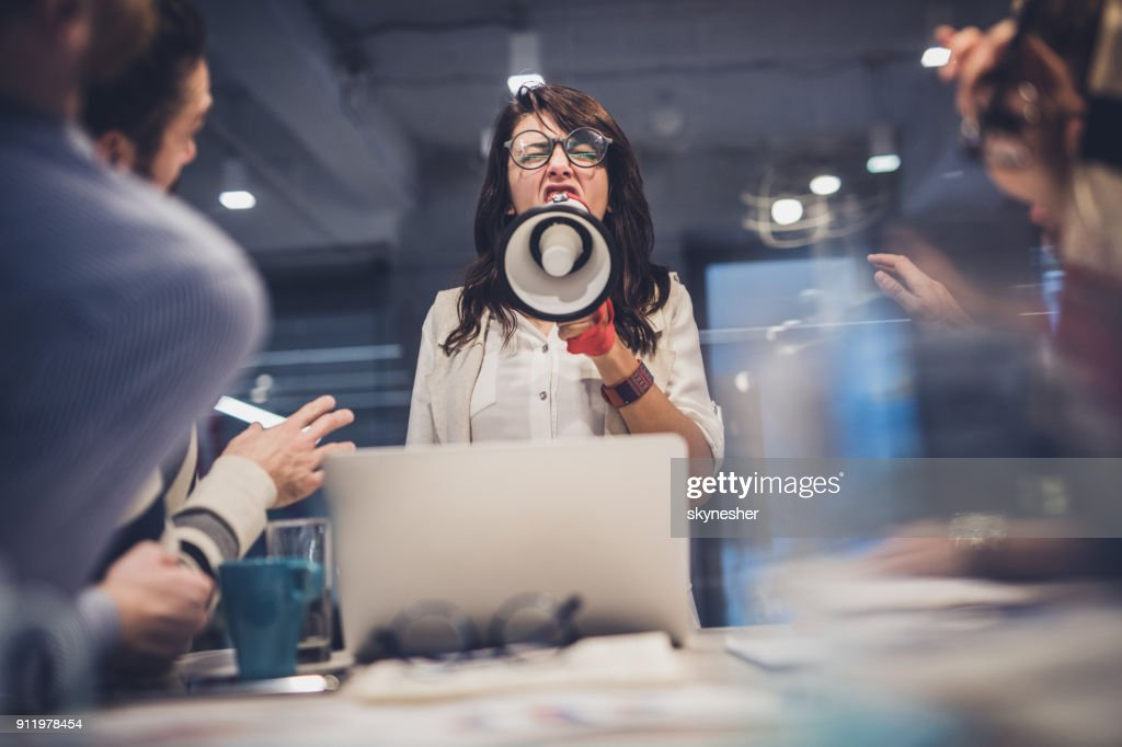 Rude female leader yelling at her coworkers through megaphone in the office. : Stock Photo