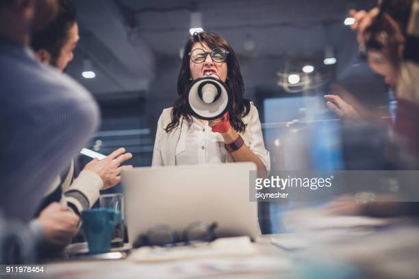 Rude female leader yelling at her coworkers through megaphone in the office.