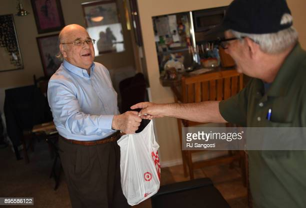 Rudi Jocobsen left takes a bag of food from Uriel Rauff who works for Jewish Family Service Colorado as a driver for the Kosher Meals on Wheels...
