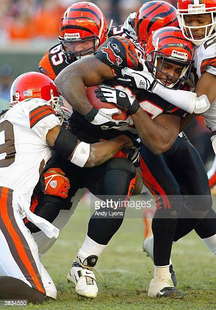 Rudi Johnson of the Cincinnati Bengals runs with the ball and is stopped by the defense of the Cleveland Browns on December 28 2003 at Paul Brown...